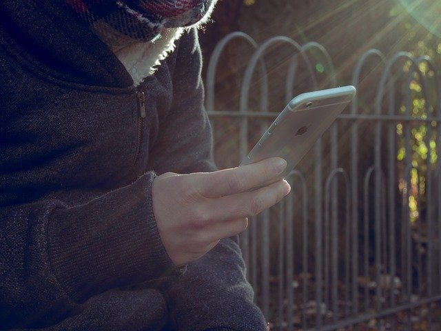seorang yang sedang memainkan Iphone miliknya