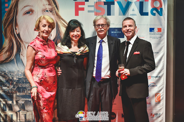 Mrs Elizabeth Galland, Ms Poh-Eng Sia, Mr. Jean-Pierre Galland, and Mr Gilles Martinez posing in front of the le French Film Festival backdrop.