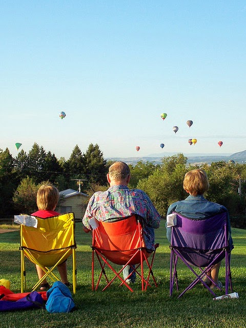 Three people on colourful folding chairs looking at skyline with hot air balloons