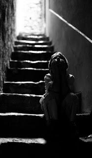 طفل صغير يجلس على سلالم ، الحزن و والعزلة الوحدة ، خلفية سوادء