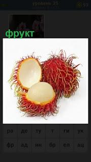 экзотический фрукт круглый и лохматый, один разрезан пополам