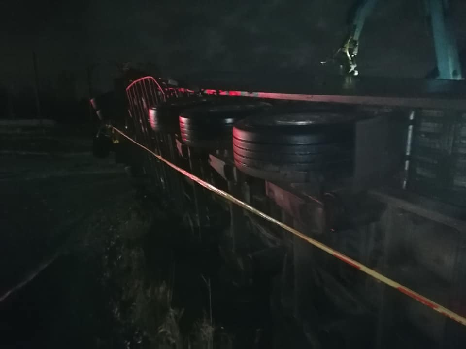 Apgāzušās uz sāna kravas mašīnas piekabes aizmugurējie riteņi