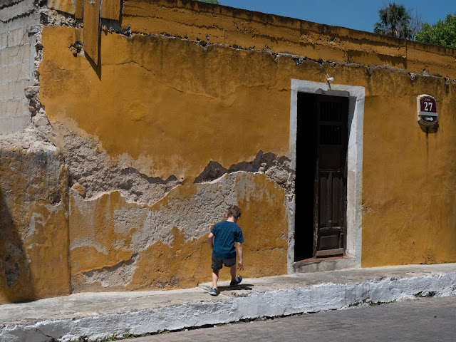 Niño de espaldas frente a fachada amarilla desconchada en Izamal