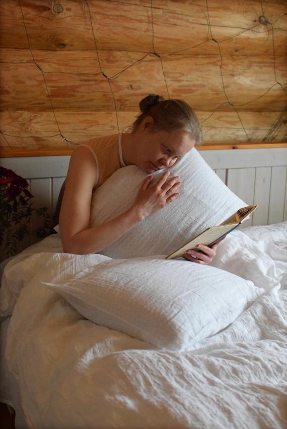 Kuvassa nainen halaa tyynyä ja lukee kirjaa sängyllä.