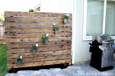 Pagar atau sekat yang terbuat dari papan ini selain berfungsi sebagai pencipta privasi, juga bisa dimanfaatkan untuk menyimpan pon tanaman. Cocok sebagai penyekat antar rumah yang jaraknya berdekatan.
