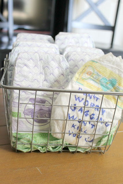 Baby shower guests write messages on diapers for late night diaper changes!