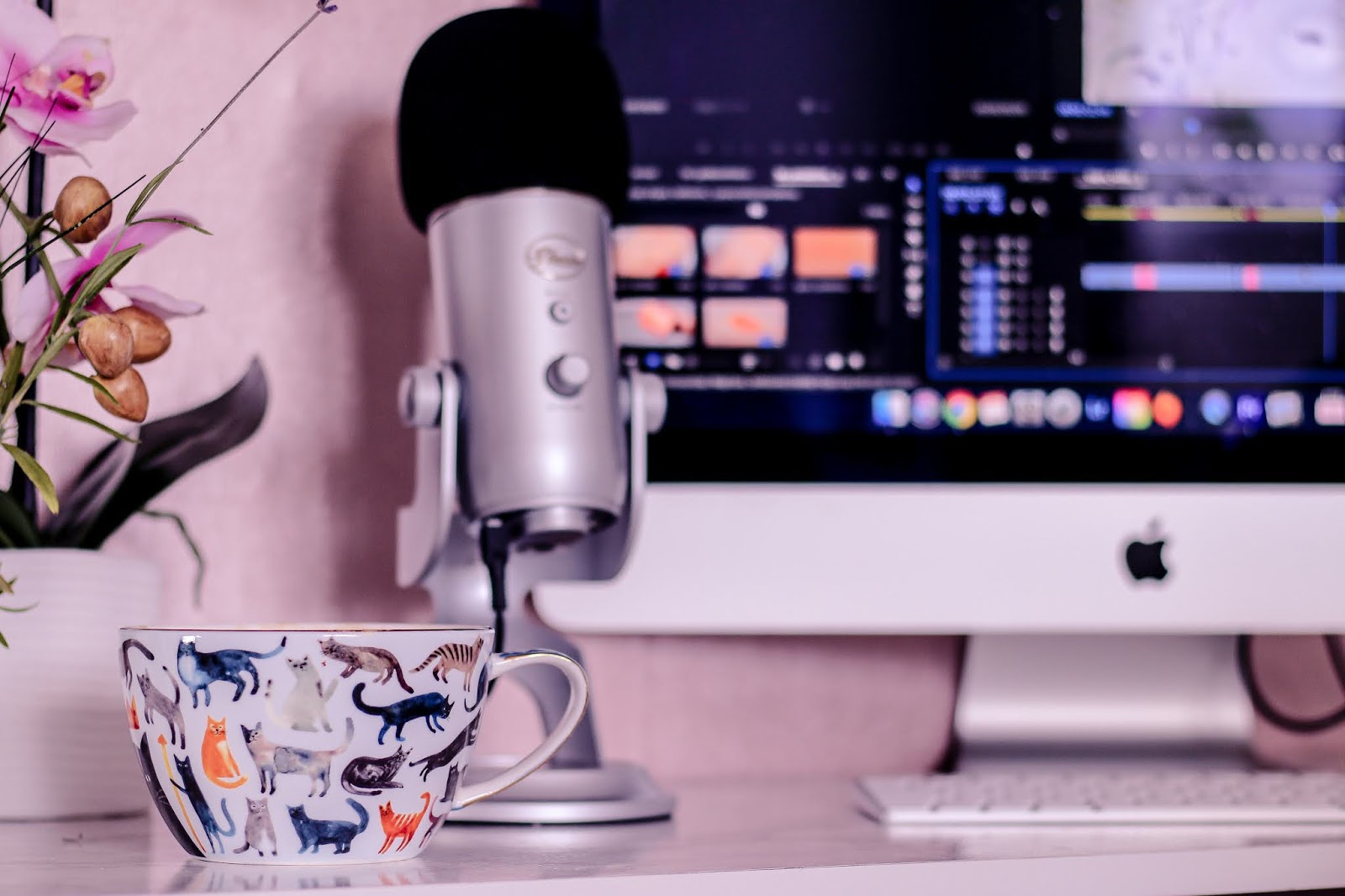 Close up photo of a white mug with ginger and black cats on it, on top of a white marble top desk with an iMac and Blue Yetti microphone in the background