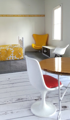 Mock-up of a one-twelfth scale modern miniature motel room with a round table and chair in the front. At the back of the room is a bed, a yellow egg chair and a sideboard under a window,