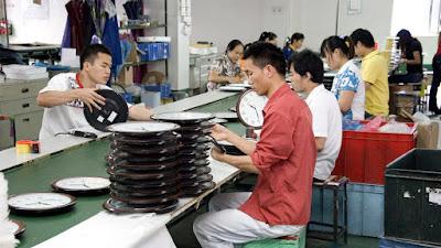 obreros en una fabrica montando partes de relojes