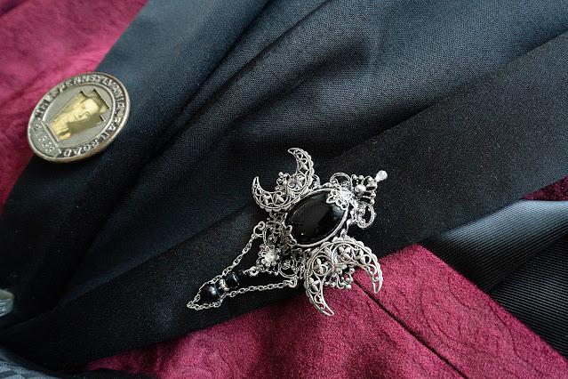 Ornate black brooch on jacket