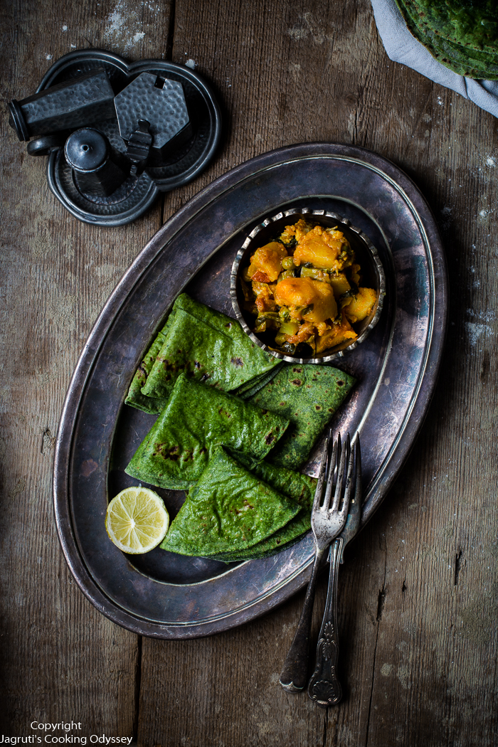 Green palak flatbreads are served with potato and cauliflower curry on a metal tray.