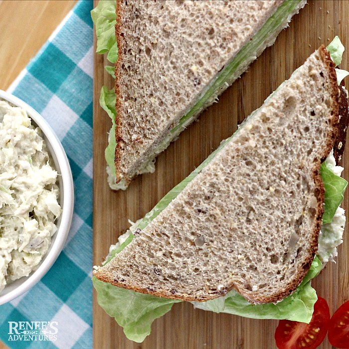 southern style chicken salad recipe in white bowl to the left and a sandwich cut diagonally on a board with Southern style chicken salad and lettuce on whole grain bread to the right