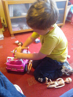 Big Boy playing with Barbies