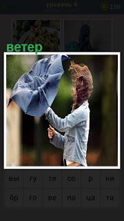 Девушка пытается открыть зонтик под сильным ветром