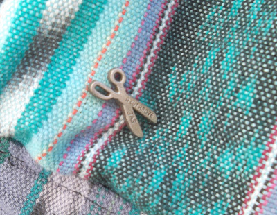 Silver-colored scissors pin bearing the words 'A Cut Above' on its upper-blade and 'JAS' on its lower. The pin is attached to resist-dyed, patterned fabric in shades of blue, purple and black