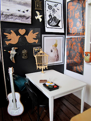 Modern dolls house miniature cafe scene, with black and white walls, wooden floor, white and beech tables, black chairs and a gallery wall of bird-related art.