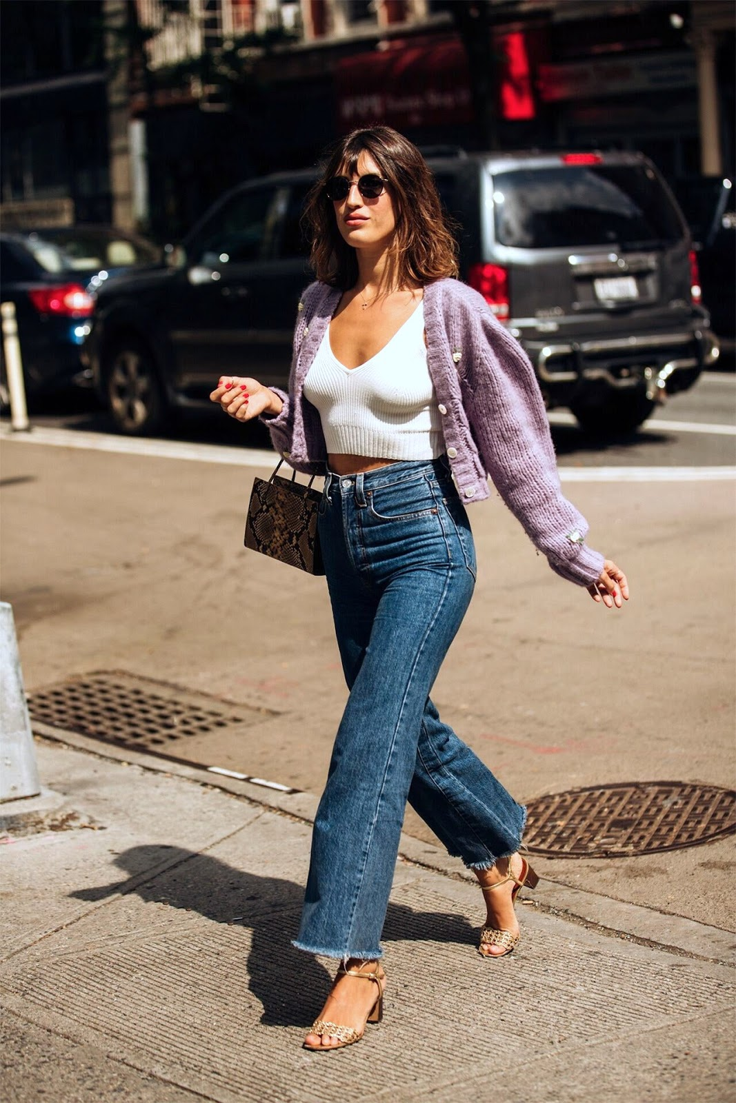 French-Girl Spring Outfit Idea — Jeanne Damas in a purple cardigan, white tank top, snake-print bag, high-waisted jeans, and sandals