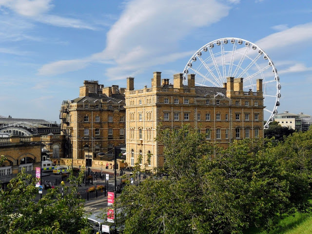 Ferris wheel and stone building in York UK