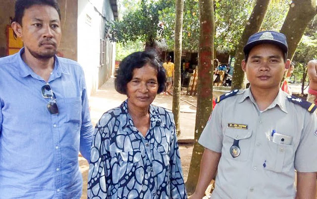 A woman stands next to authorities on Tuesday after she was arrested for human trafficking in Tbong Khmum province. Photo supplied