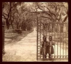 two slave girls standing behind bars of fully open gate