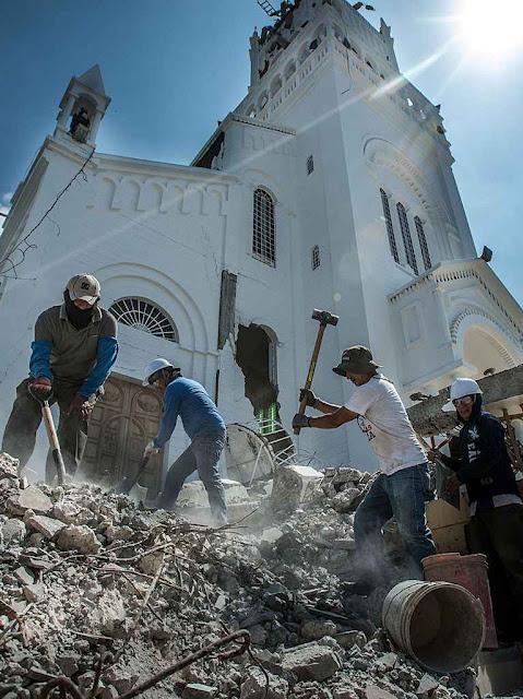Voluntários nos escombros da torre da Basílica em Montecristi