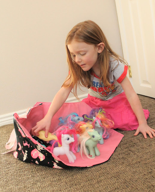 Little girl with fold out toy box and ponies