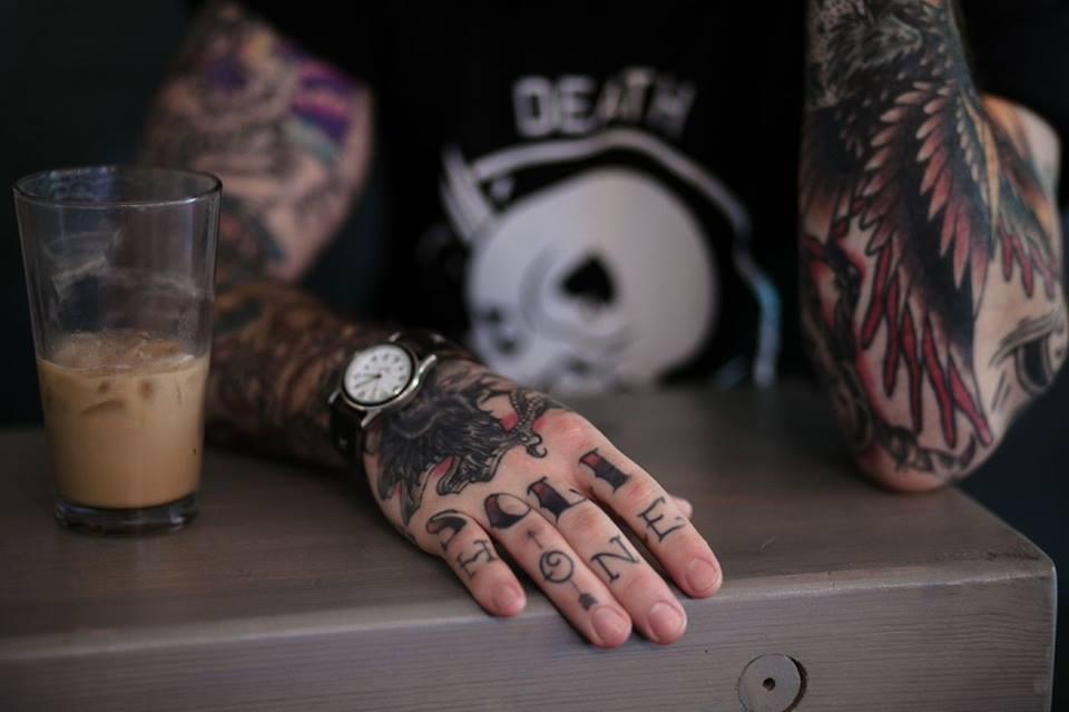 Vemos a un chico en la barra de un bar, en su mano tatuajes de letras