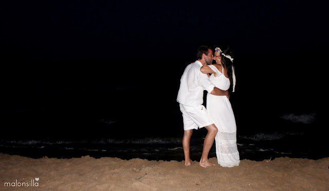 Pareja de novios con look blanco para boda ibicenca en la playa abrazados.