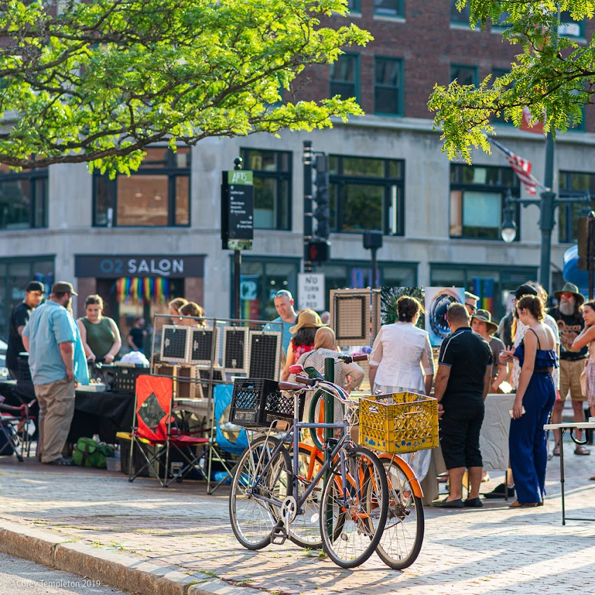 Portland, Maine USA July 2019 photo by Corey Templeton. Bicycles and artwork on the sidewalk during a First Friday.