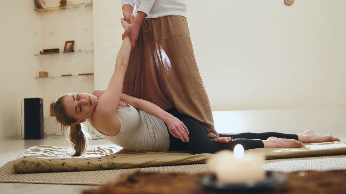 A male Thai Yoga Massage Therapist performing a spinal twist on a female client.