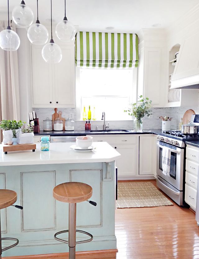Touches of Spring decor in the kitchen with teal kitchen island and green Roman shade