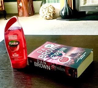 A bright red semicircular bottle that says Radox in bright white font with Red Apple & Pomegranate in smaller white font next to a rectangular book saying dan brown in white font on a brown rectangular table  on a bright background