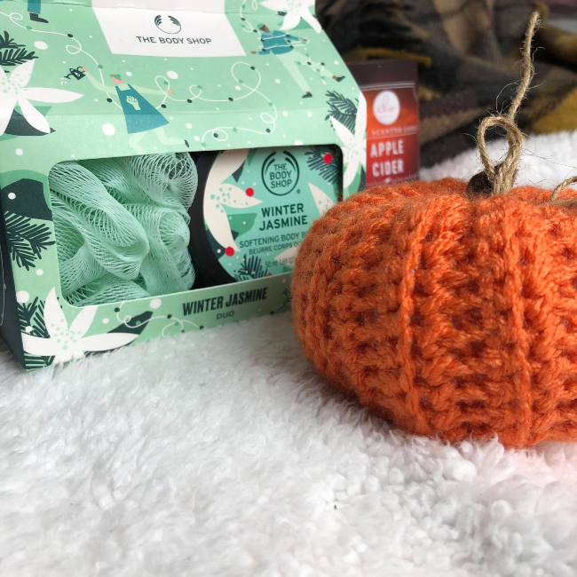 Mint green carboard pack containing a body buff and round tub of body butter. Next to a crocheted pumpkin