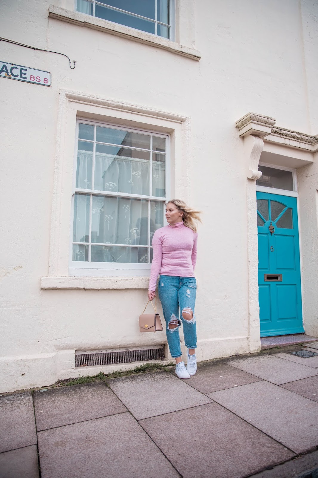 Rachel Emily in a pink top and jeans outside a cream house with a blue door
