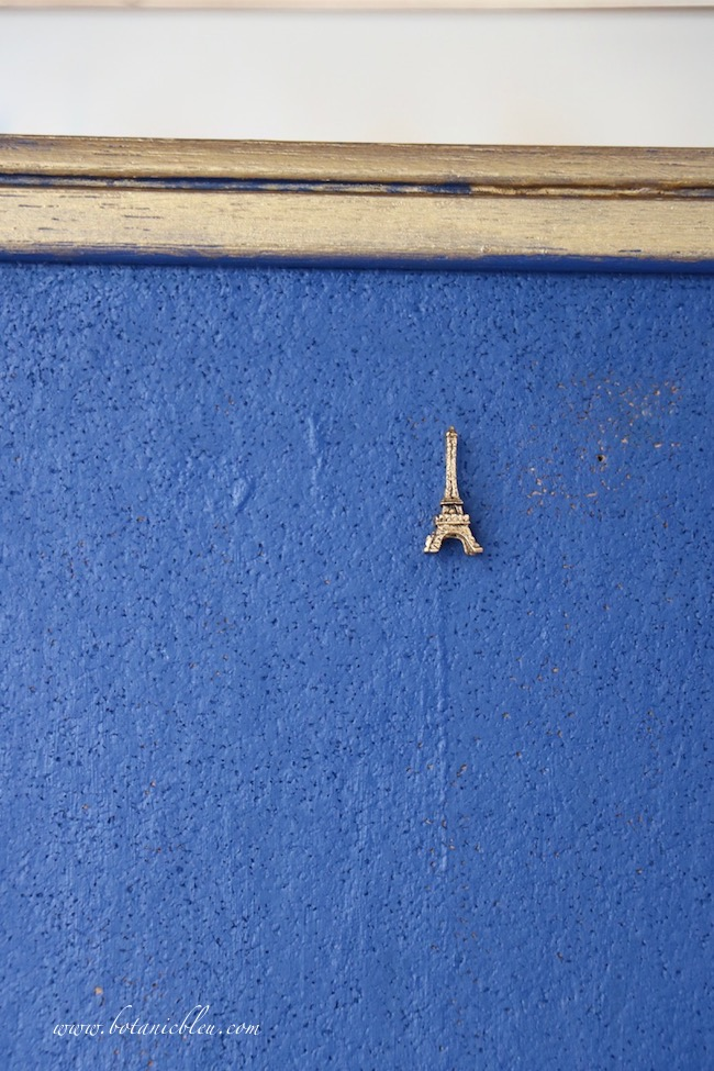 Inked Blue Bulletin Board Debut shows a cork board can display 3-D objects like Eiffel Tower tacks