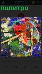Несколько кисточек и краска, палитра для написания картин. Весь стол испачкан краской