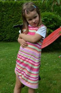Kind hält etwas in der Hand, das es nicht teilen will