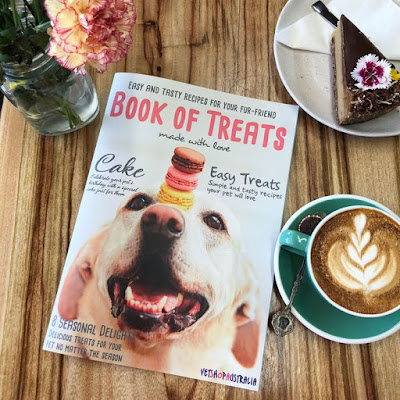 A picture of the VetShopAustralia Book of Treats on a table surrounded by a piece of cake, a cup of coffee and some flowers in a vase
