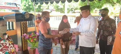Bupati Malra M. Thaher Hanubun saat menyerahkan Bantuan Sosial Tunai kepada Keluarga Penerima Manfaat