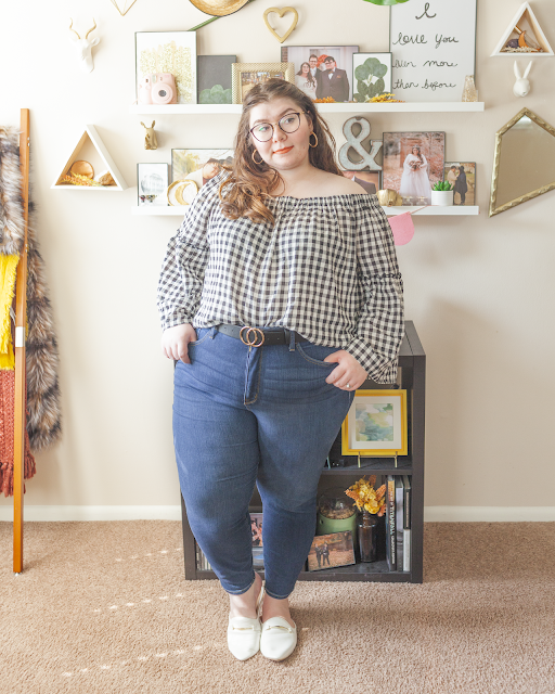 An outfit consisting of a gingham off the shoulder blouse with long angel sleeves, tucked into dark wash high waist skinny jeans and white mules.