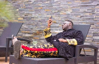Medikal relaxing comfortably in his house.