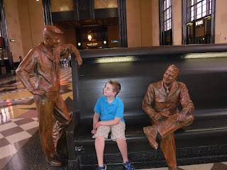 a blonde boy in a blue polo shirt sits next to a statue of a WWII soldier about to board a train to head to training, while looking up at another statue, also a WWII soldier shipping out, at the Durham Museum in Omaha, Nebraska