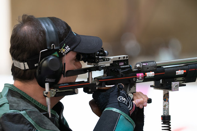 Alexandre Galgani, com protetor de ouvido, tem a arma na mão e mira