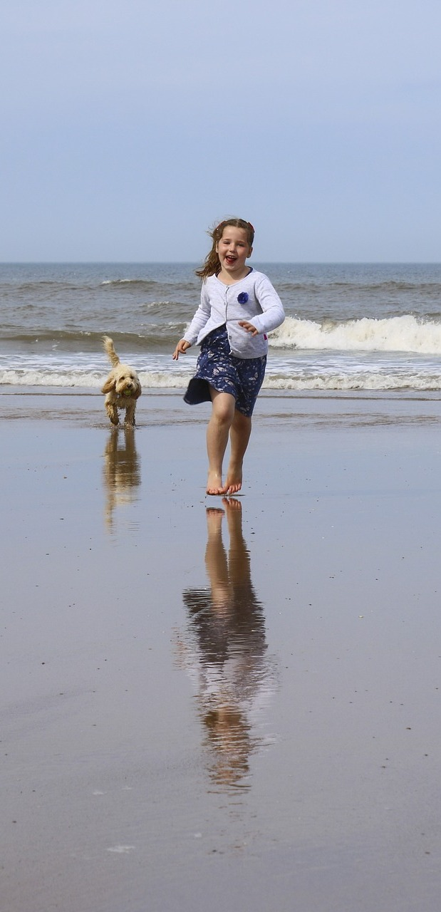 A girl running with a dog.