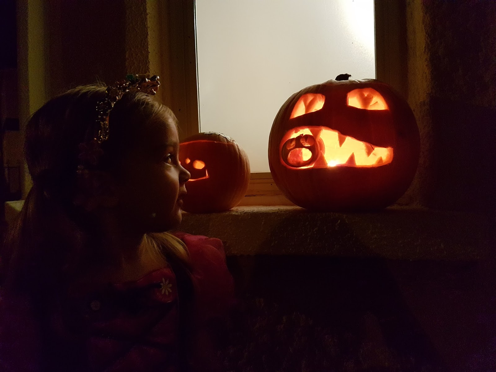 toddler looking at a jack o lantern in dark