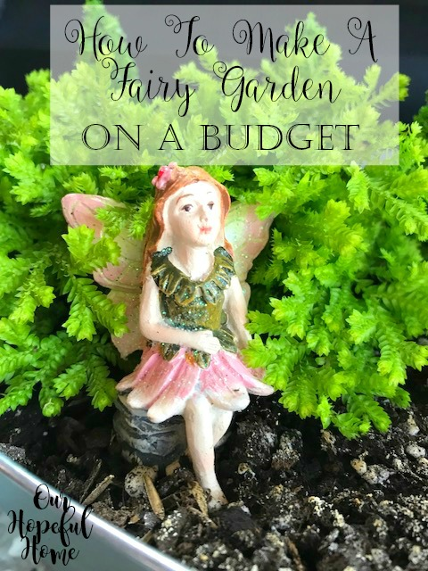 ceramic fairy sitting in fairy garden green plants