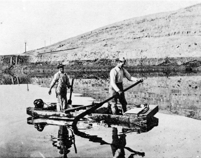 Two men raft on a pool of oil.