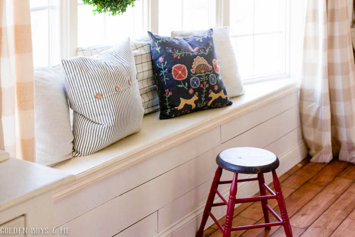 Throw pillows in dining room window seat with wall planking