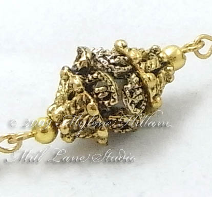 """Ornate gold """"bead cap bead"""" made up of several layers of bead caps"""