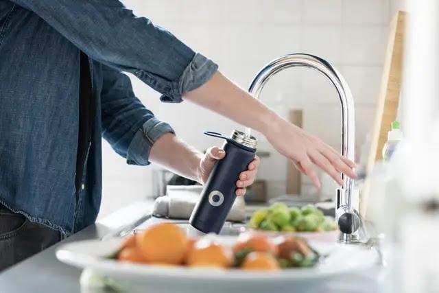 Una mujer en una cocina con un termo en la mano llenándolo de agua directamente del grifo